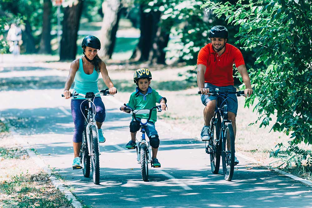Family - a lady, a man and a boy - biking in a park