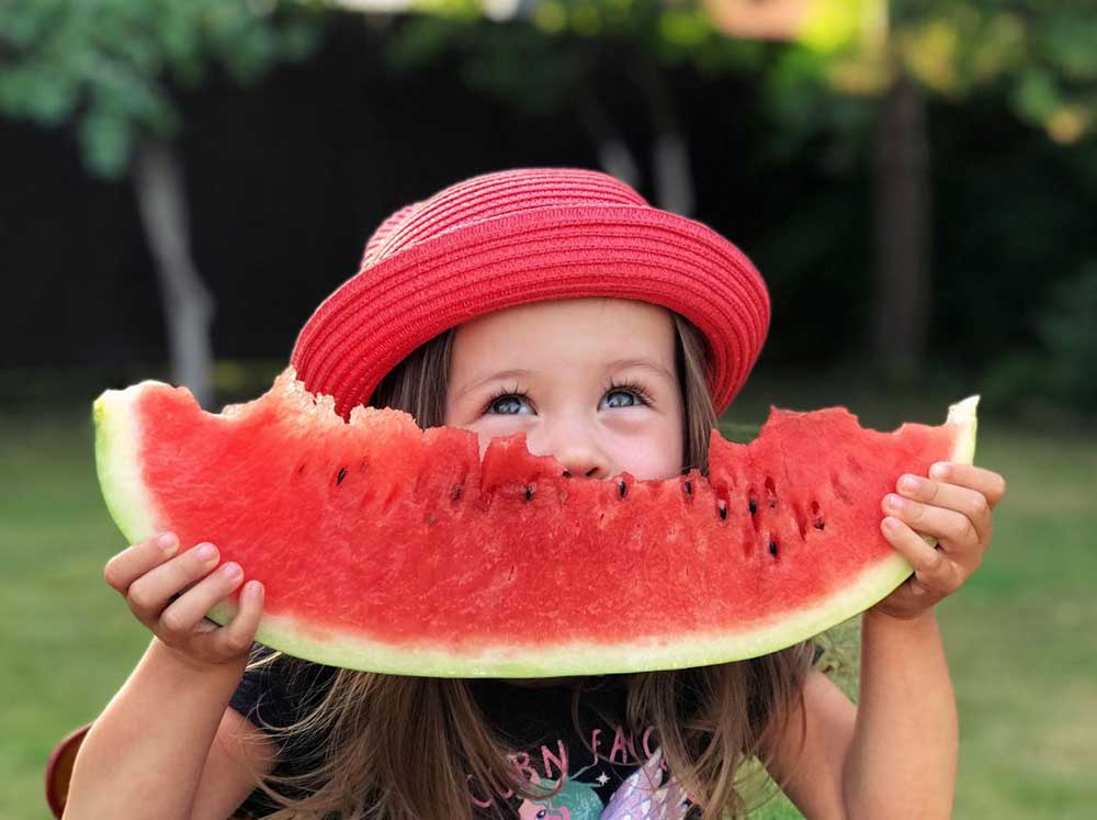 Girl smiling eating a watermelon slice